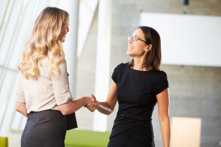 дві жінки тиснуть руки