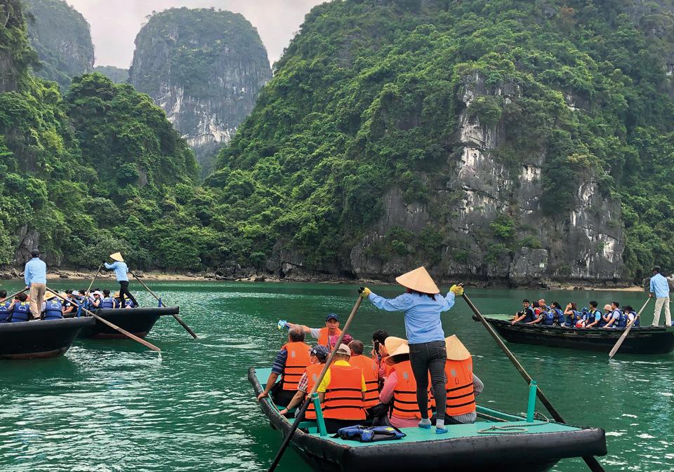 Люди на лодке плывут среди гор по реке