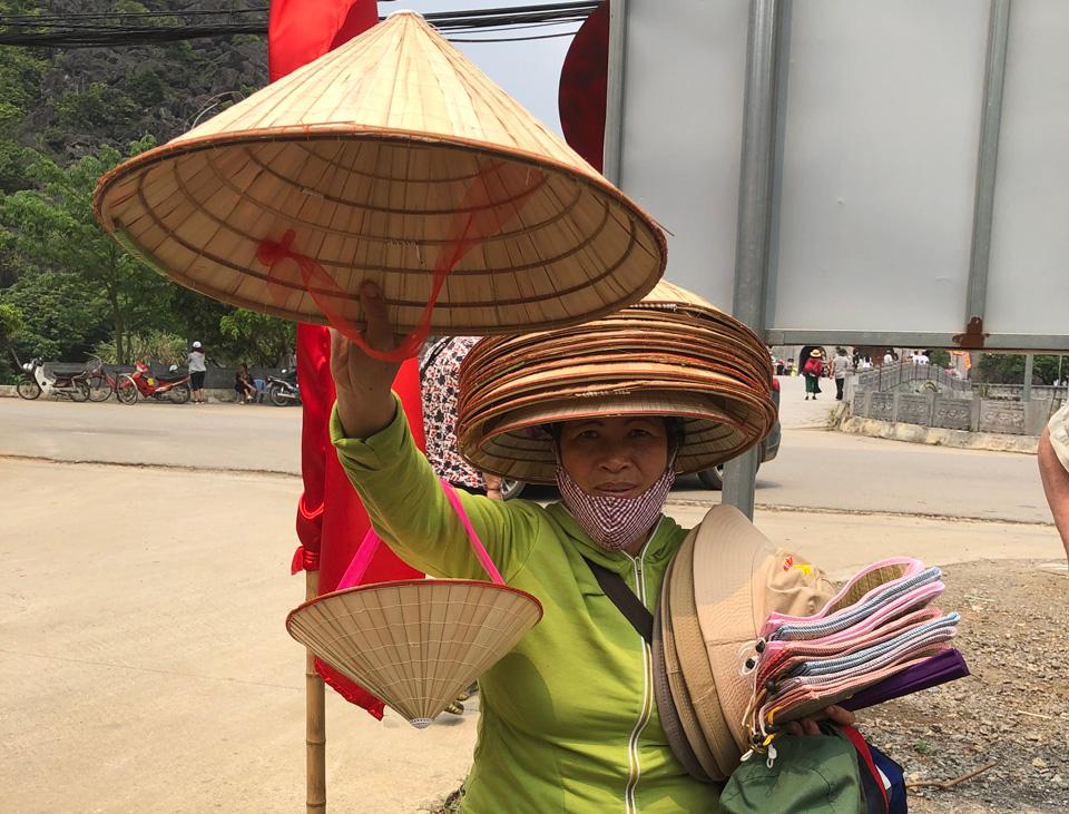 Женщина на улице продает шапки