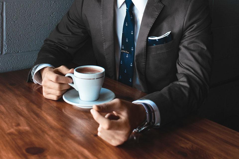 мужчина в пиджаке с чашкой кофе