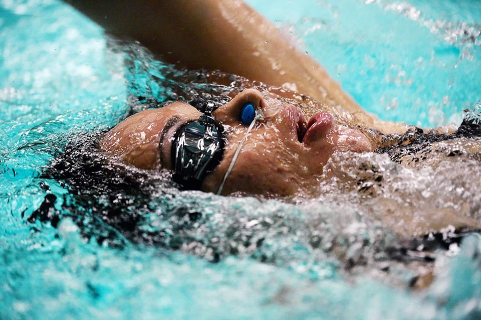 жінка пливе в басейні
